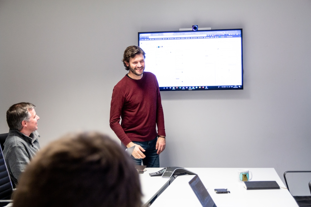 Man presenting in front of a screen to other group members