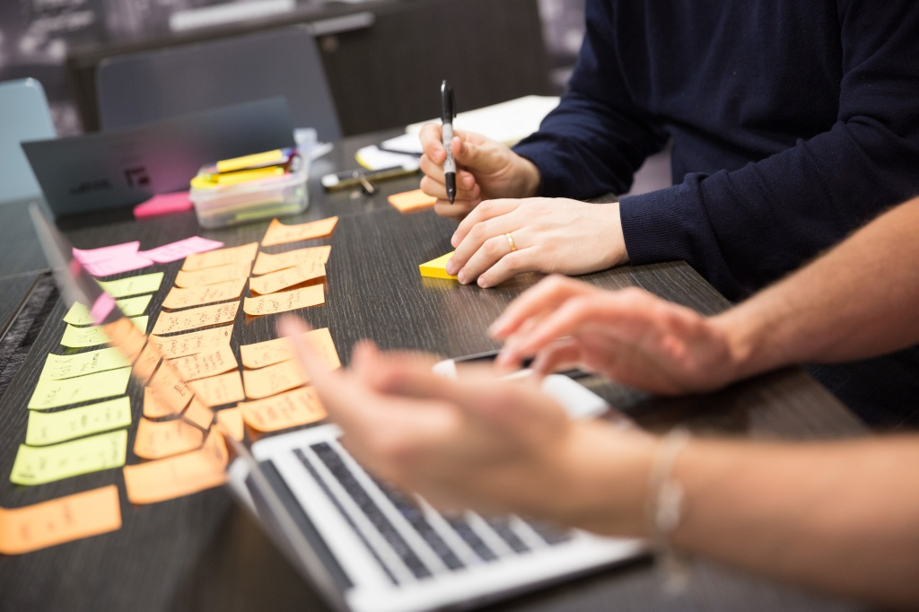 Two people writing on post-it notes with a laptop in the foreground