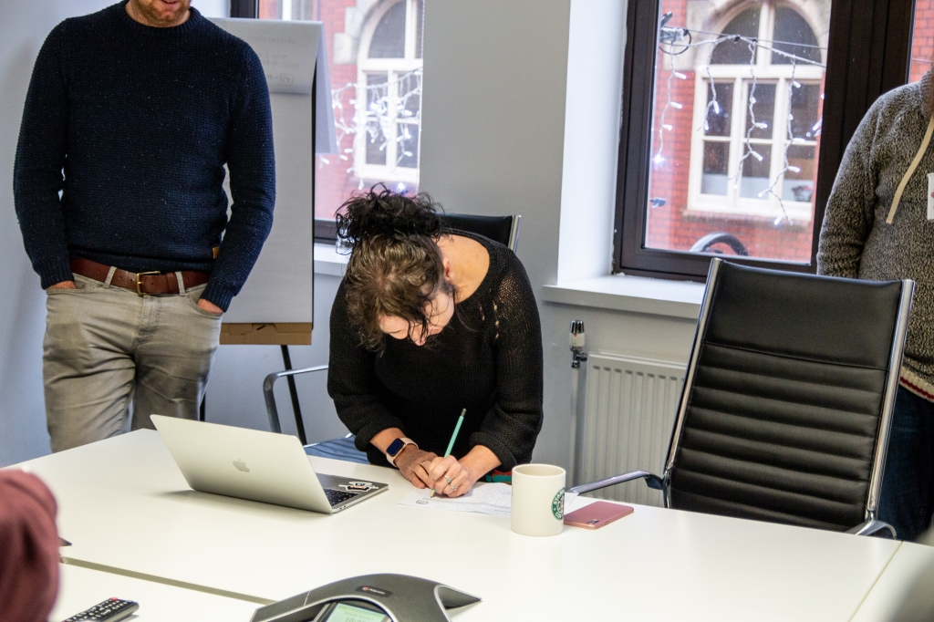 Woman writing on a piece of paper with a laptop, while others stand and watch