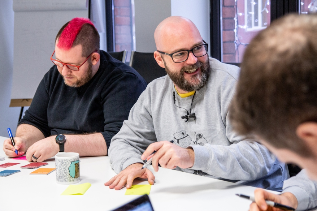 Group of people writing on post-it notes at a table