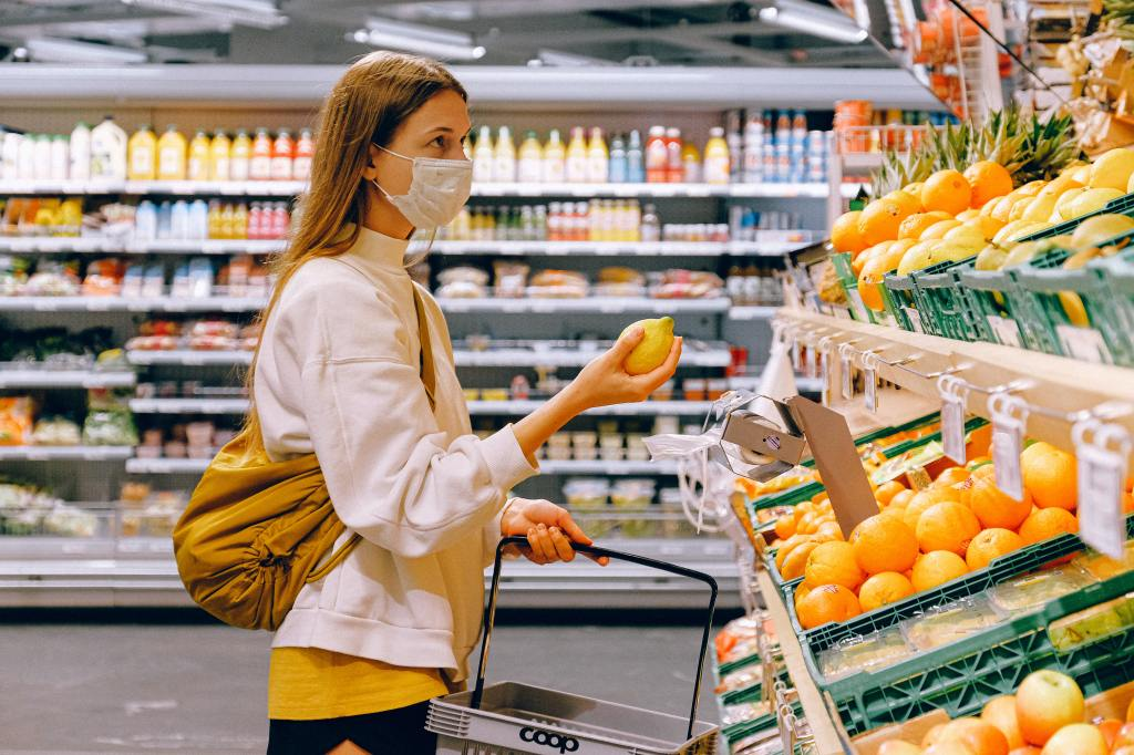Woman wearing a face mask in a supermarket, looking at a display of fruit
