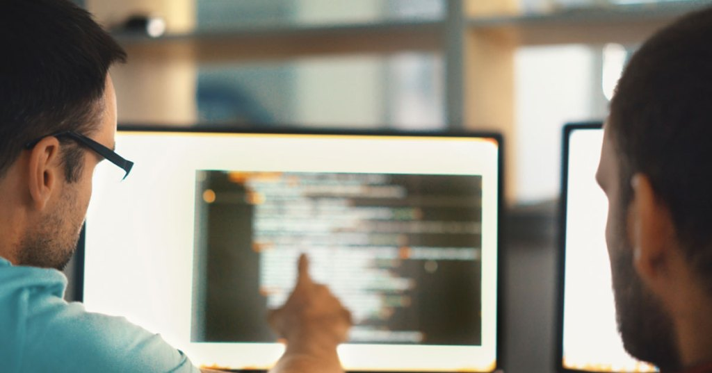 Software professionals reviewing code on a screen
