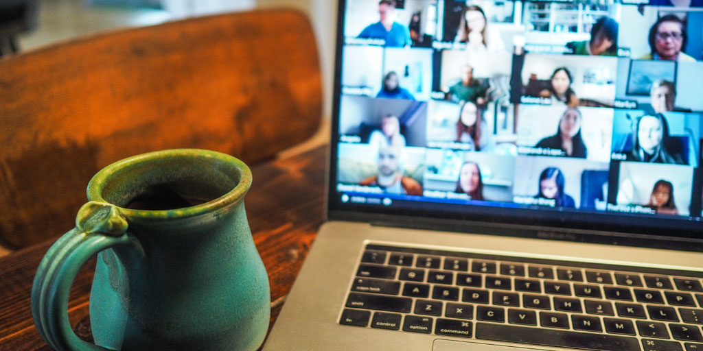 Open laptop with a multi-person video conference call taking place, and a mug of coffee in the foreground