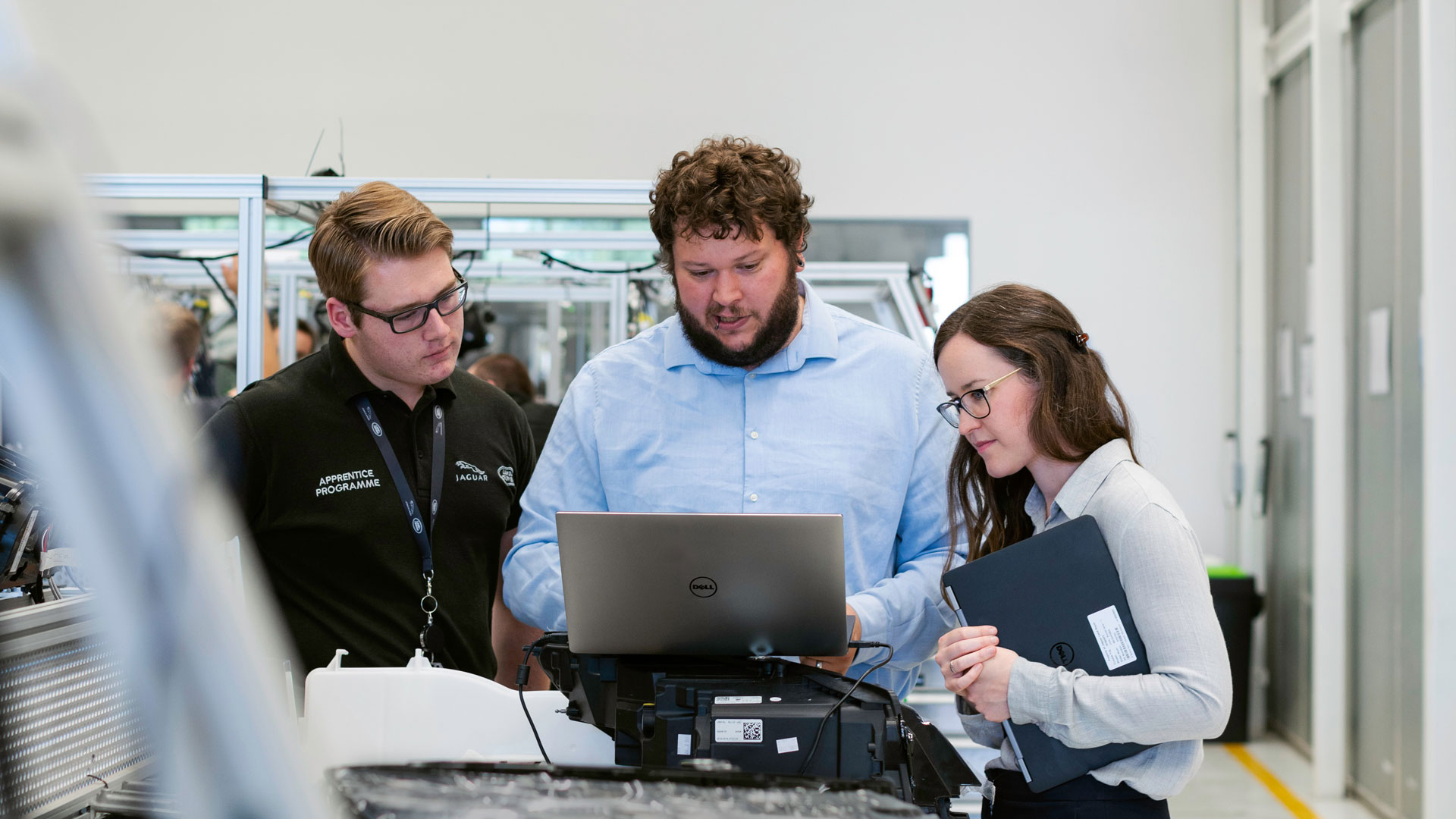 Three people in factory environment, looking at a laptop screen