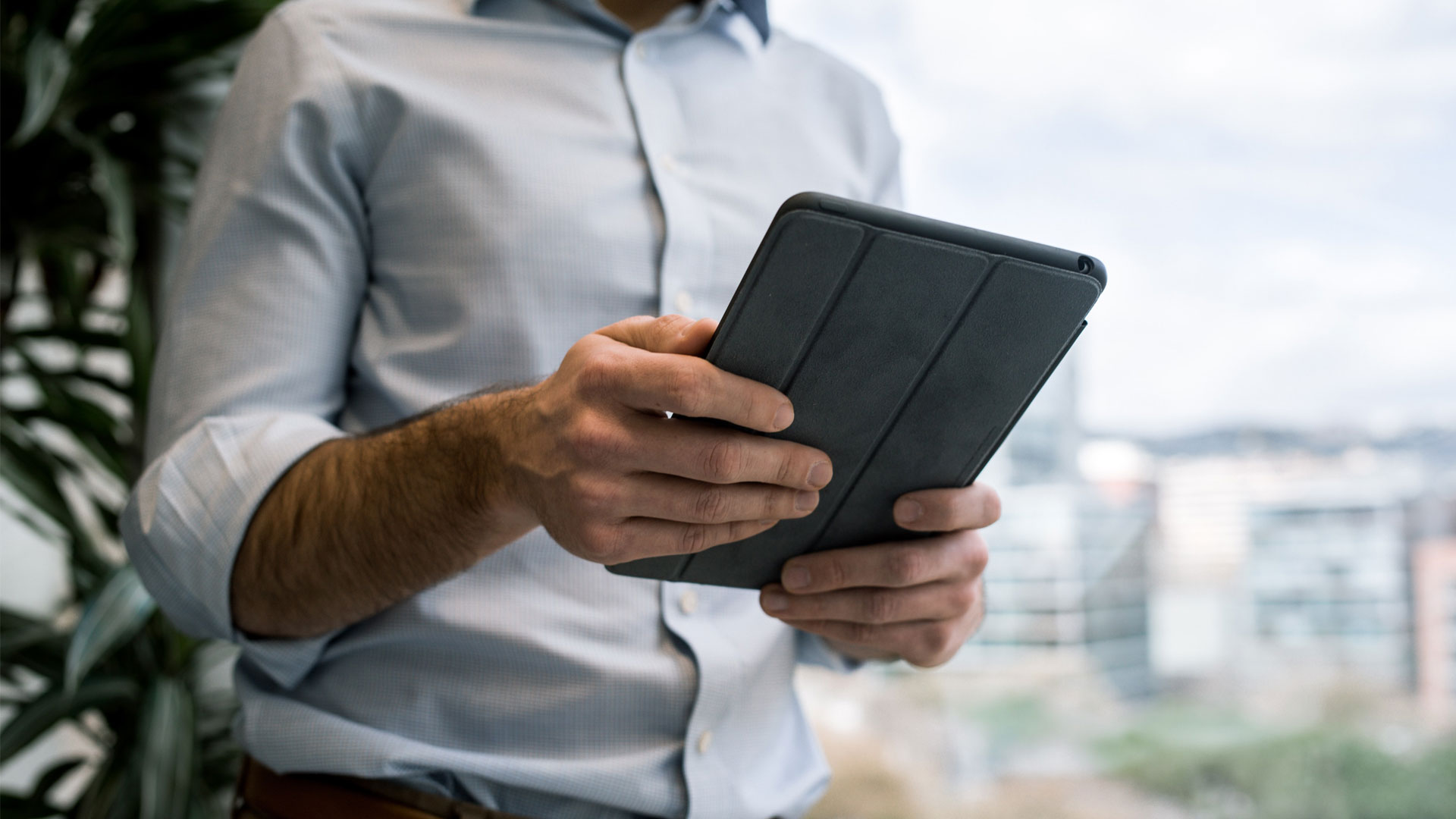 Man using iPad, shown from the neck down