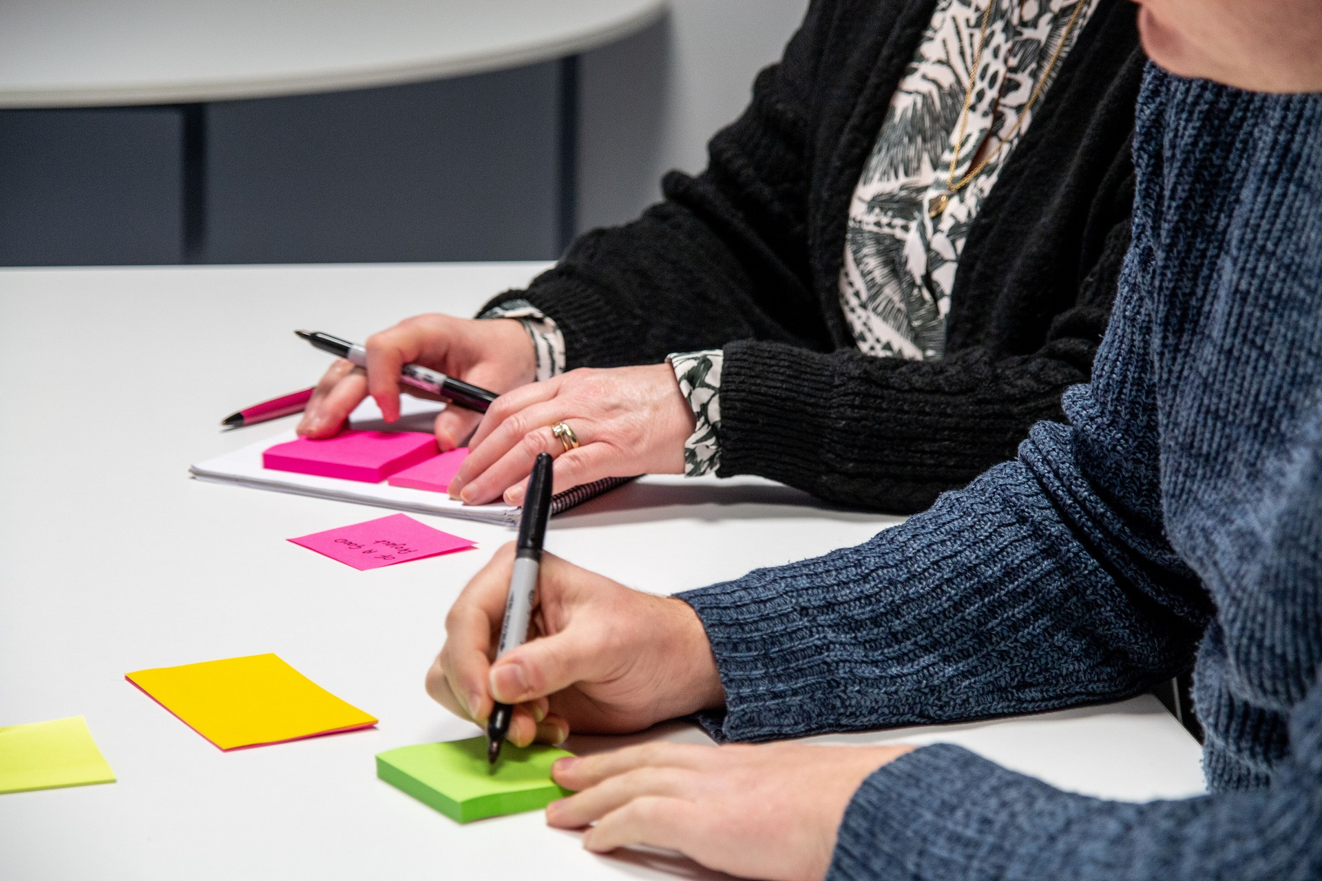 Abstract shot of people writing on post-it notes
