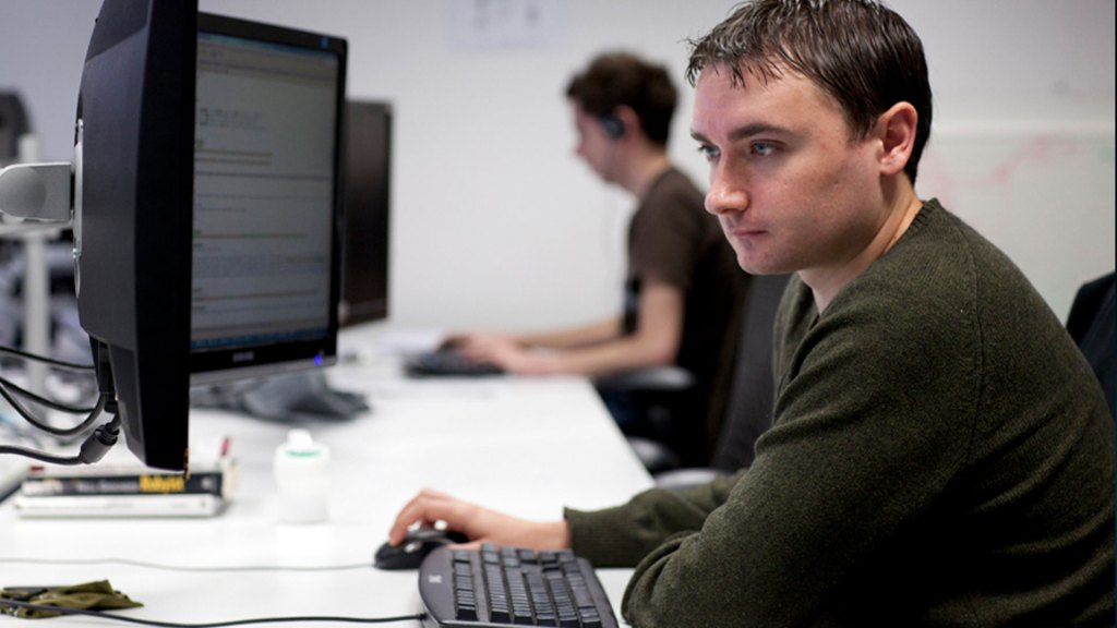 Developer looking at two monitors