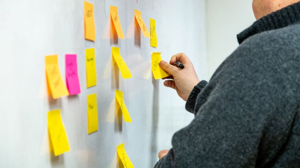Person sticking post-it notes to a wall