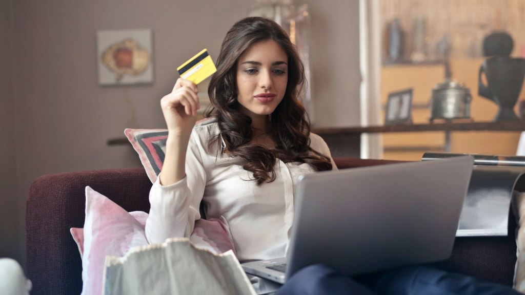 Woman on sofa with laptop, holding a credit card