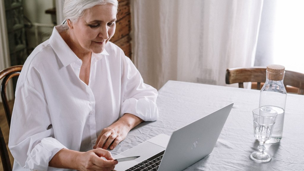 Woman holding credit card in front of laptop, with water jug and glass