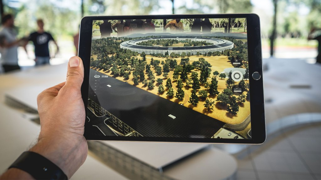 Person's hand holding a tablet device with augmented reality showing development plans for a new building