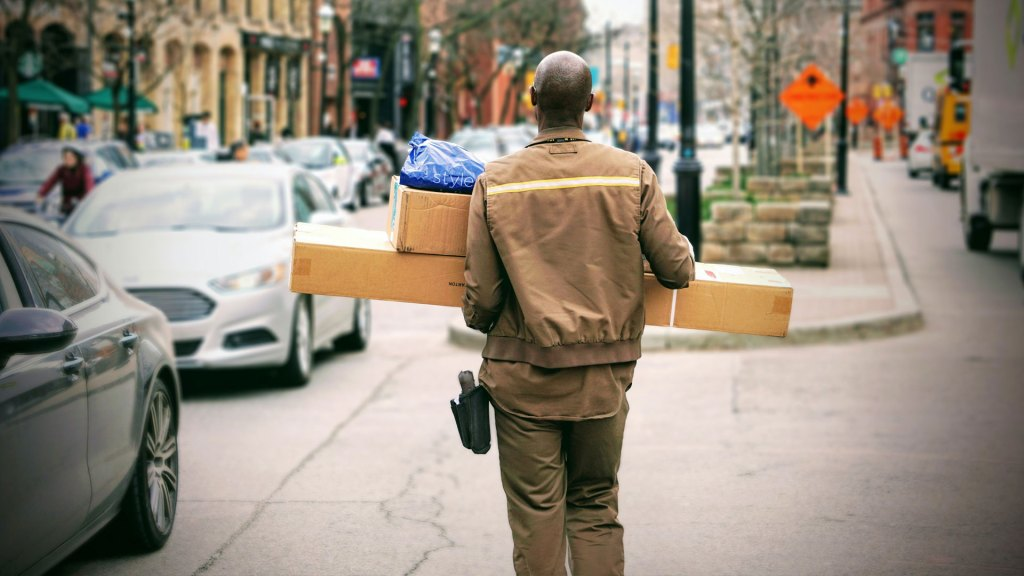 Back of a delivery man with parcels