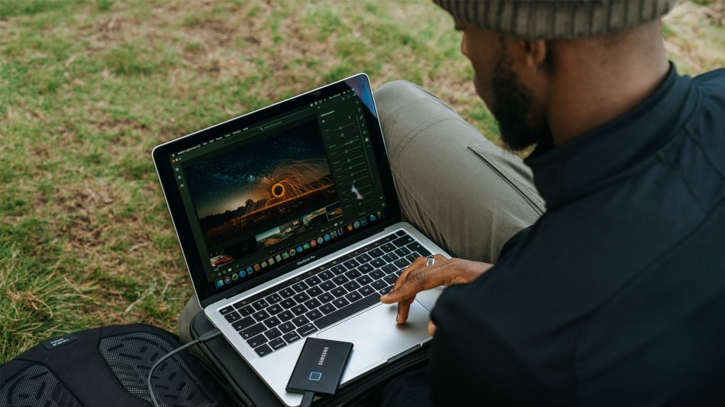 Person using a laptop to edit photos, outdoors