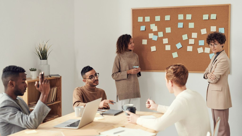 Group of people working around a corkboard with post-it notes