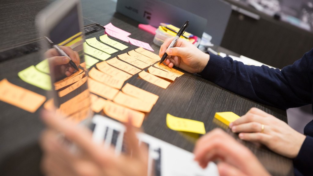 Table covered in post-it notes, with person writing on post-its and someone working on a laptop in foreground
