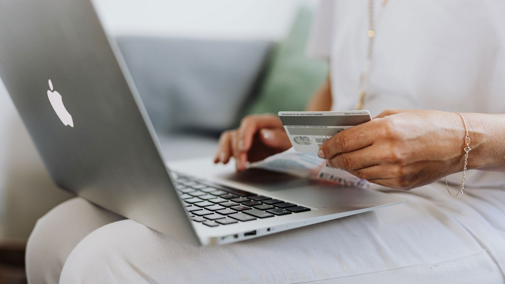 Closeup of person's hand with credit card, in front of laptop