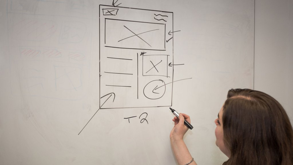 Person sketching out ideas for a web page
