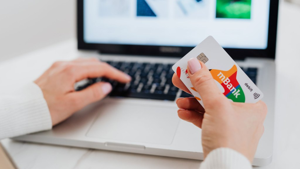 Close up of person holding credit card and using laptop