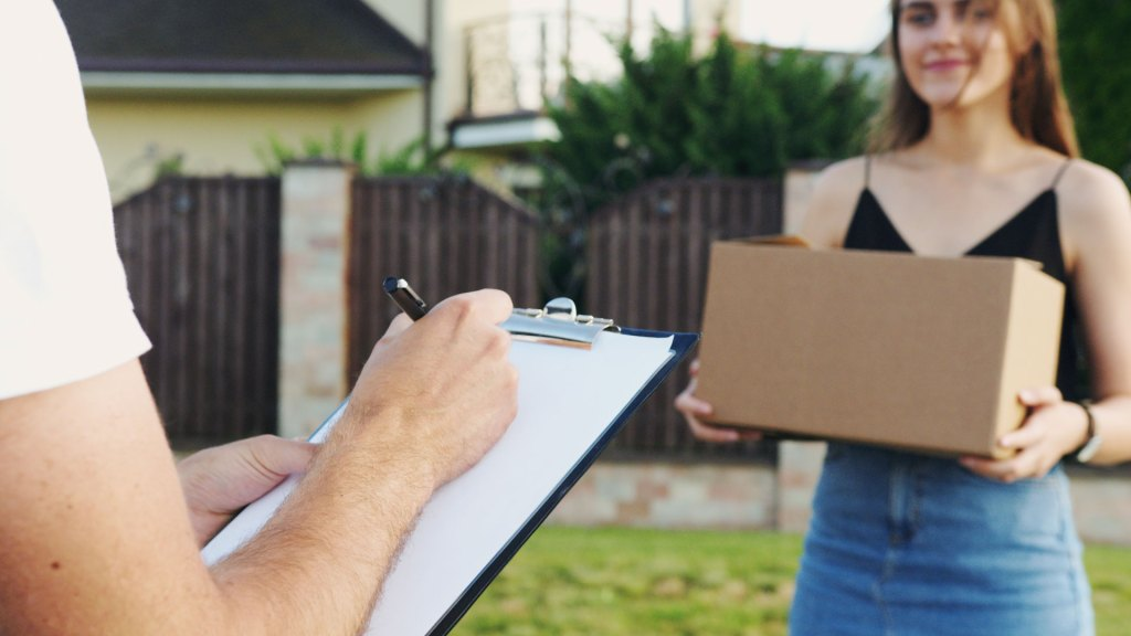 Woman holding delivery box, with person holding clipboard in foreground