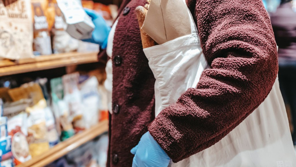Abstract shot of person browsing food shop, with full tote bag