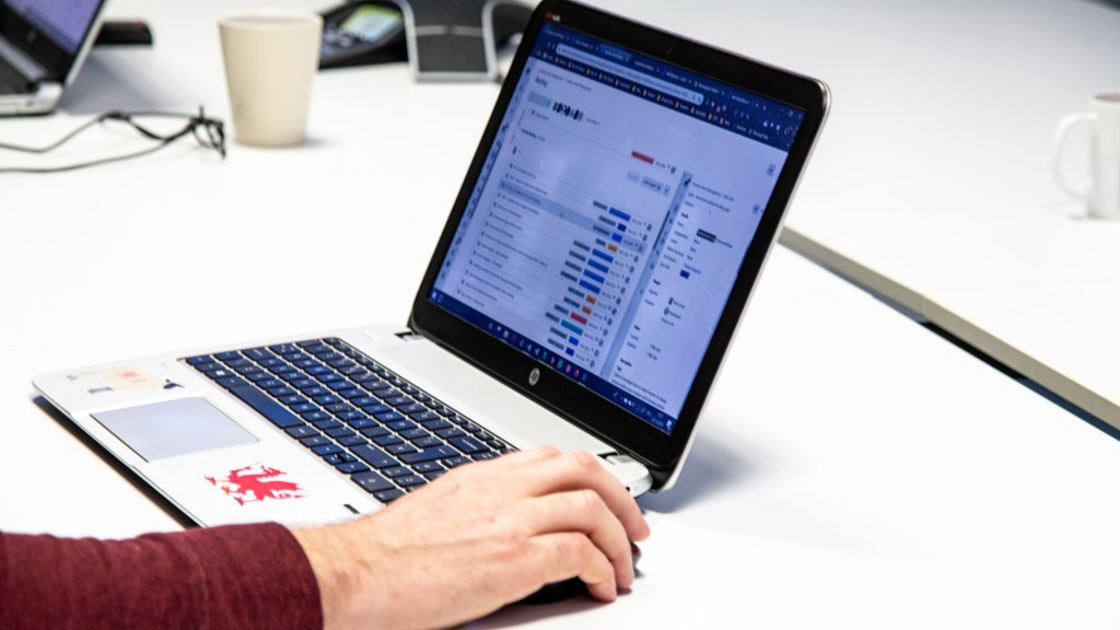 Close-up of laptop and person's hand