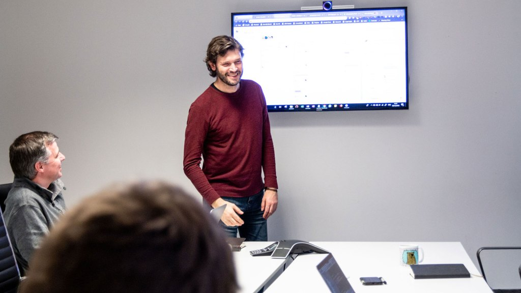 Person walking through project board at meeting
