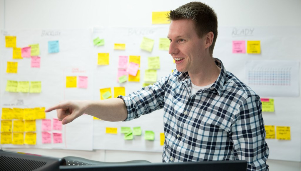 Consultant pointing with post-it notes mapped in background