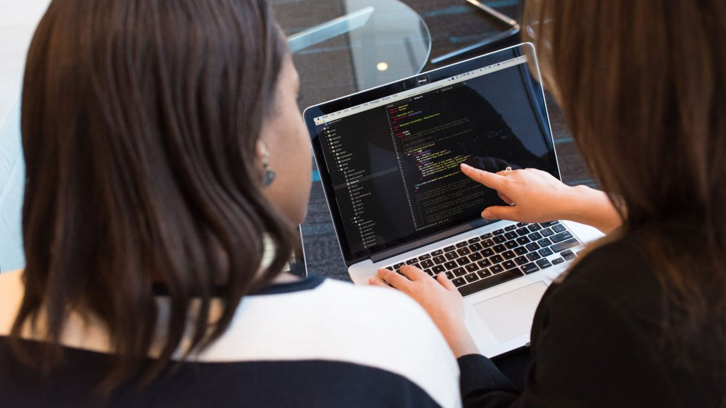 Two people looking at a screen with code on it