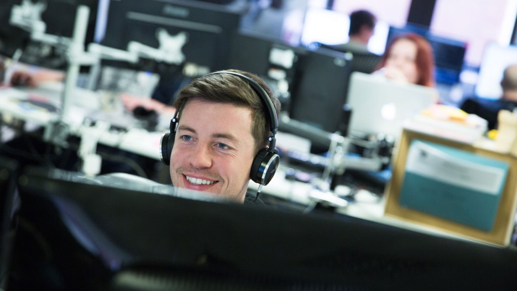 Person working in front of screen with headphones