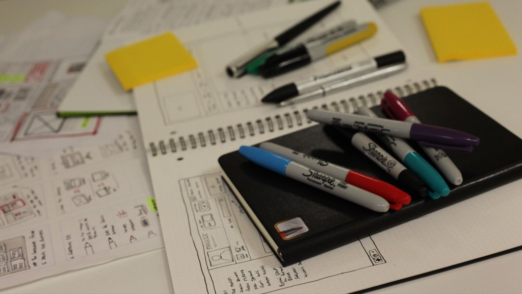 Closeup of designs, notepads and pens