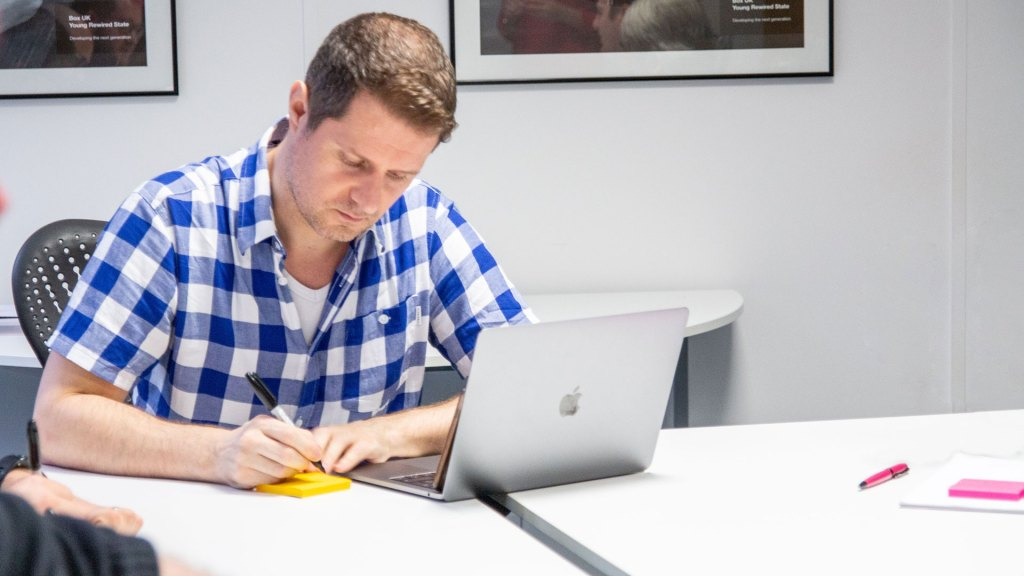 Person writing on a post-it note in front of a laptop