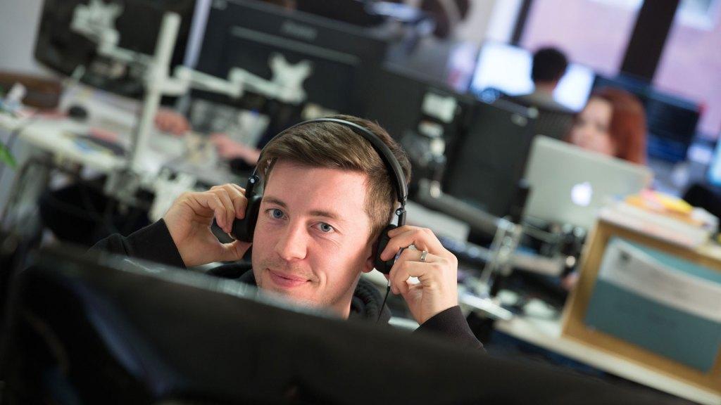 Developer with headphones looking into camera