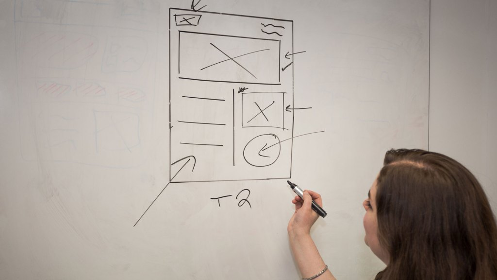 Person drawing out page design on a whiteboard